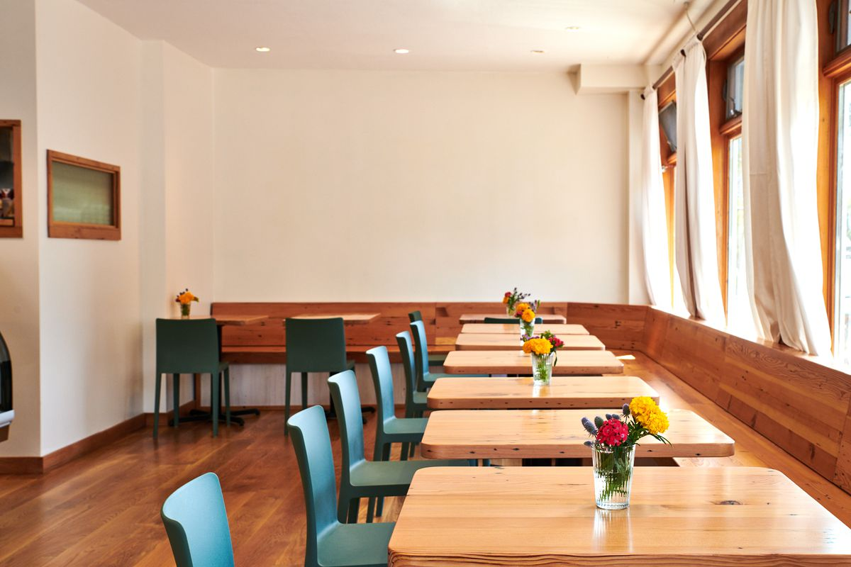 Teal seats add a pop of color along a row of two-tops