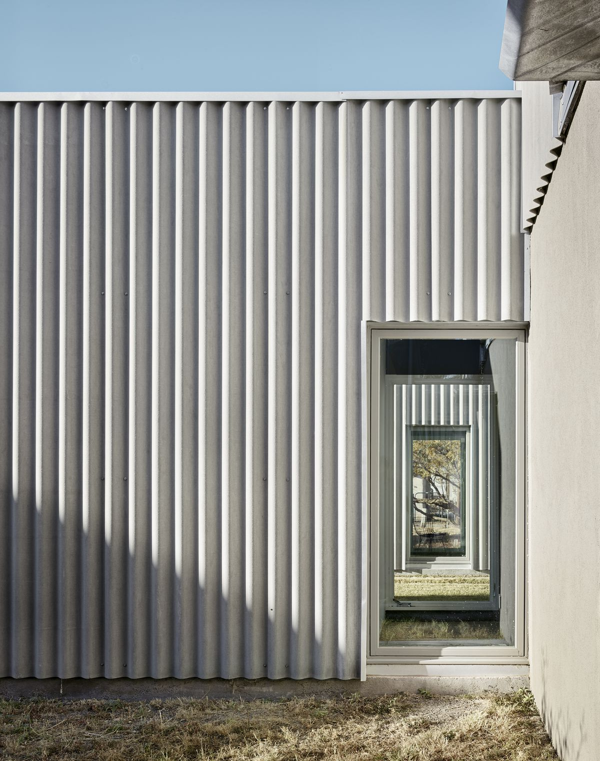 A corrugated, gray siding covers the new part of the building.
