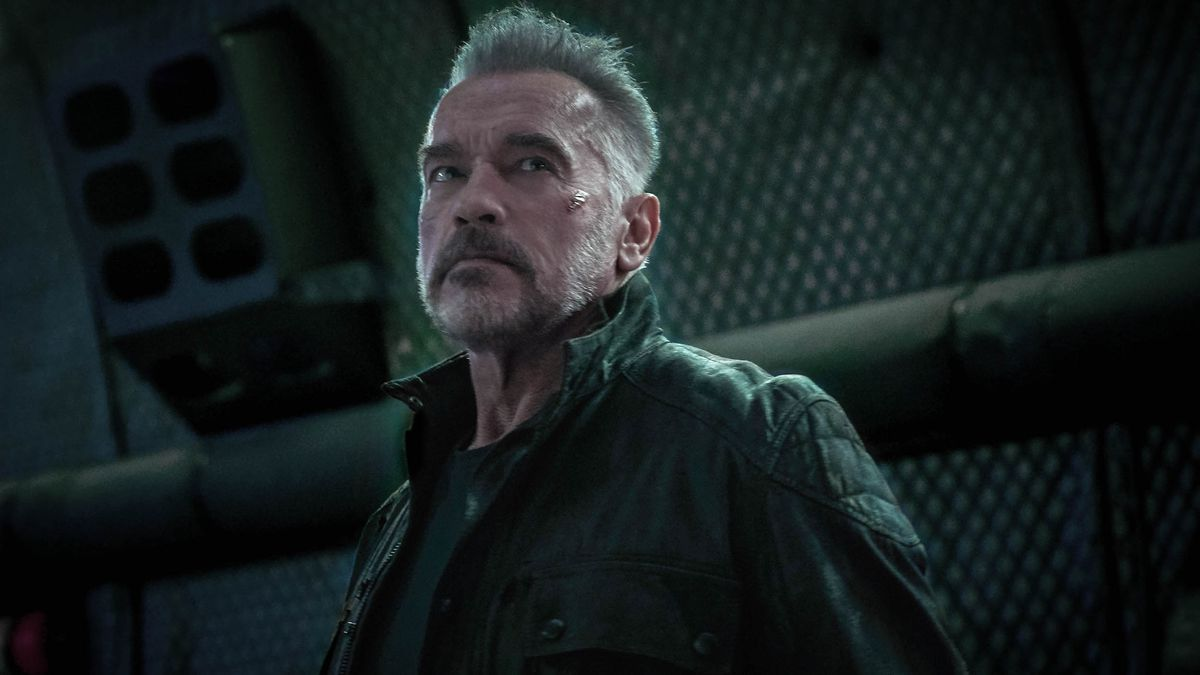 An older, gray-haired T-800, Arnold Schwarzenegger, dressed in a leather jacket.