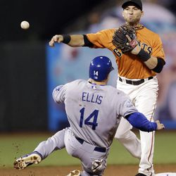 San Francisco Giants second baseman Marco Scutaro, top, throws to first after forcing out Los Angeles Dodgers' Mark Ellis on a ground ball from Shane Victorino during the fifth inning of a baseball game Friday, Sept. 7, 2012, in San Francisco. Victorino was safe at first.