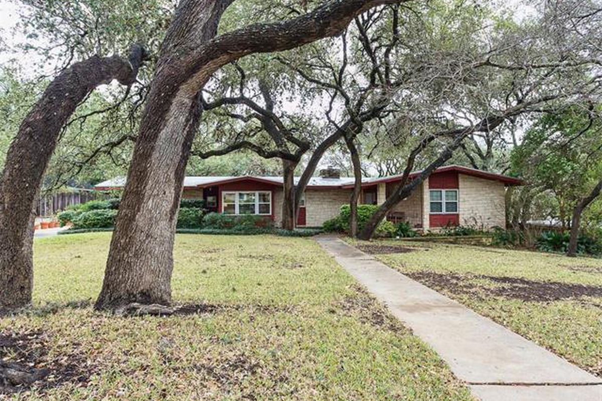 One-story brick midcentury ranch style with red trim, big trees in front, set back