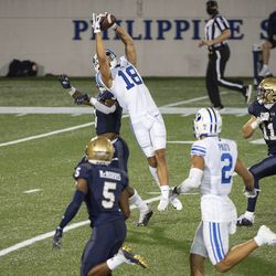 BYU wide receiver Gunner Romney (18) leaps to catch a pass over Navy defensive back Cameron Kinley during the second half of an NCAA college football game, Monday, Sept. 7, 2020, in Annapolis, Md.