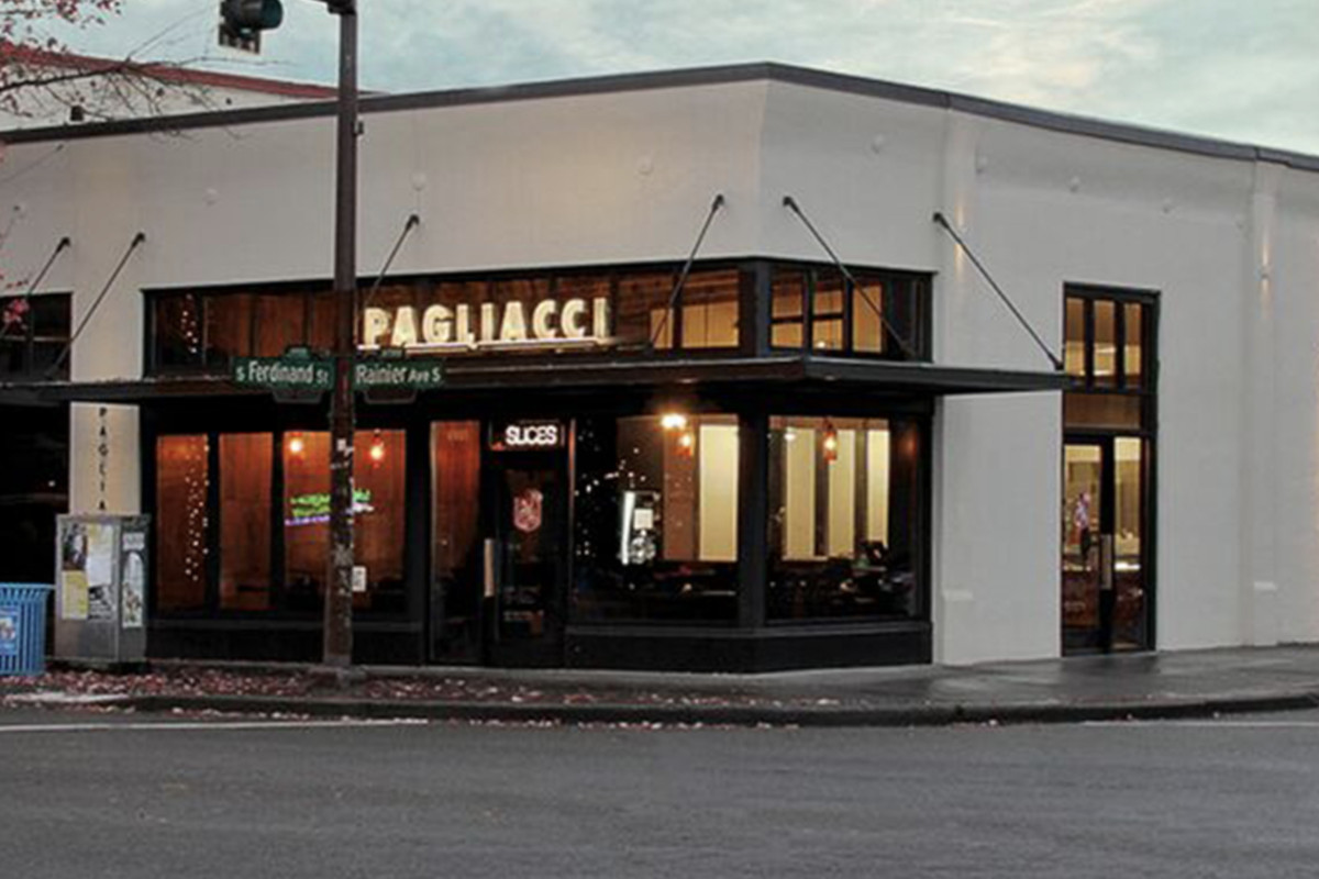 The storefront of a Pagliacci Pizza location on Rainier Avenue S in Seattle, with the restaurant's sign lit up