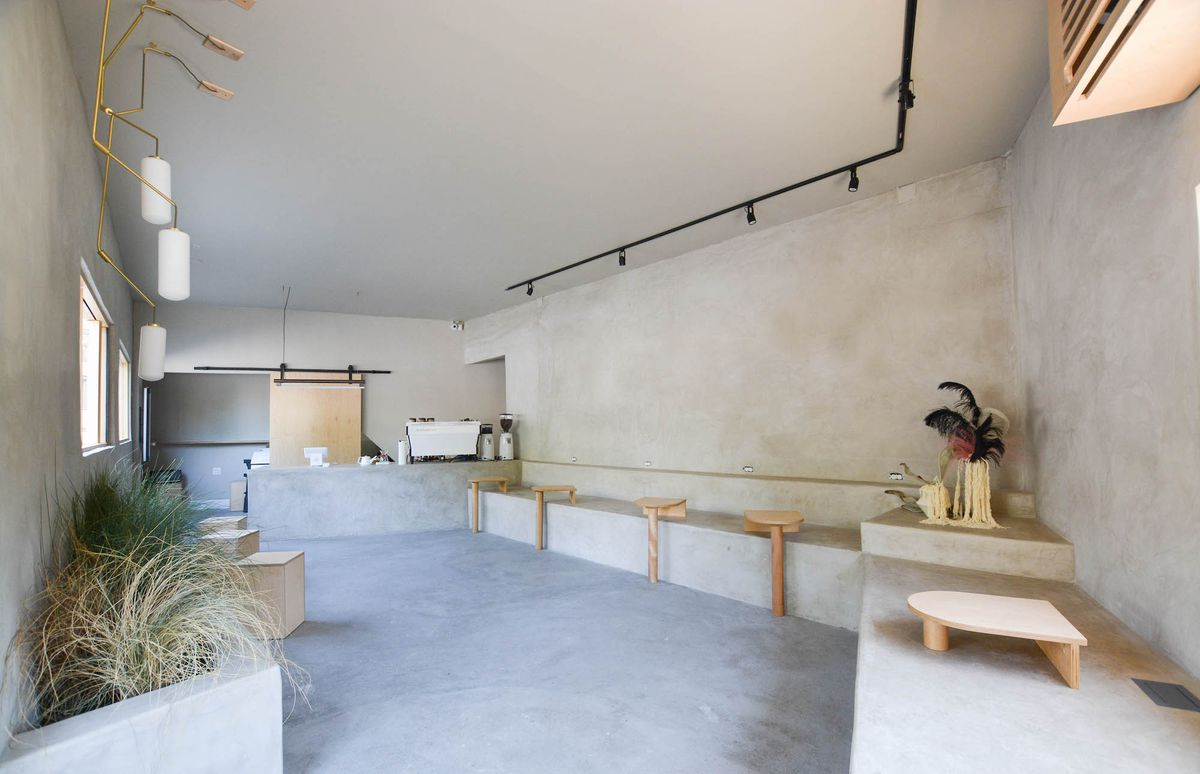 A pared-down cement room for coffee, with espresso machine in the back.