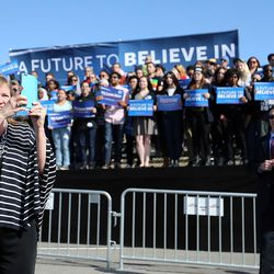 The wife of Democratic presidential candidate and Vermont Sen. Bernie Sanders, Jane, takes a photo with her phone while her husband gives a speech to supporters at This is the Place Heritage Park in Salt Lake City, Friday, March 18, 2016.