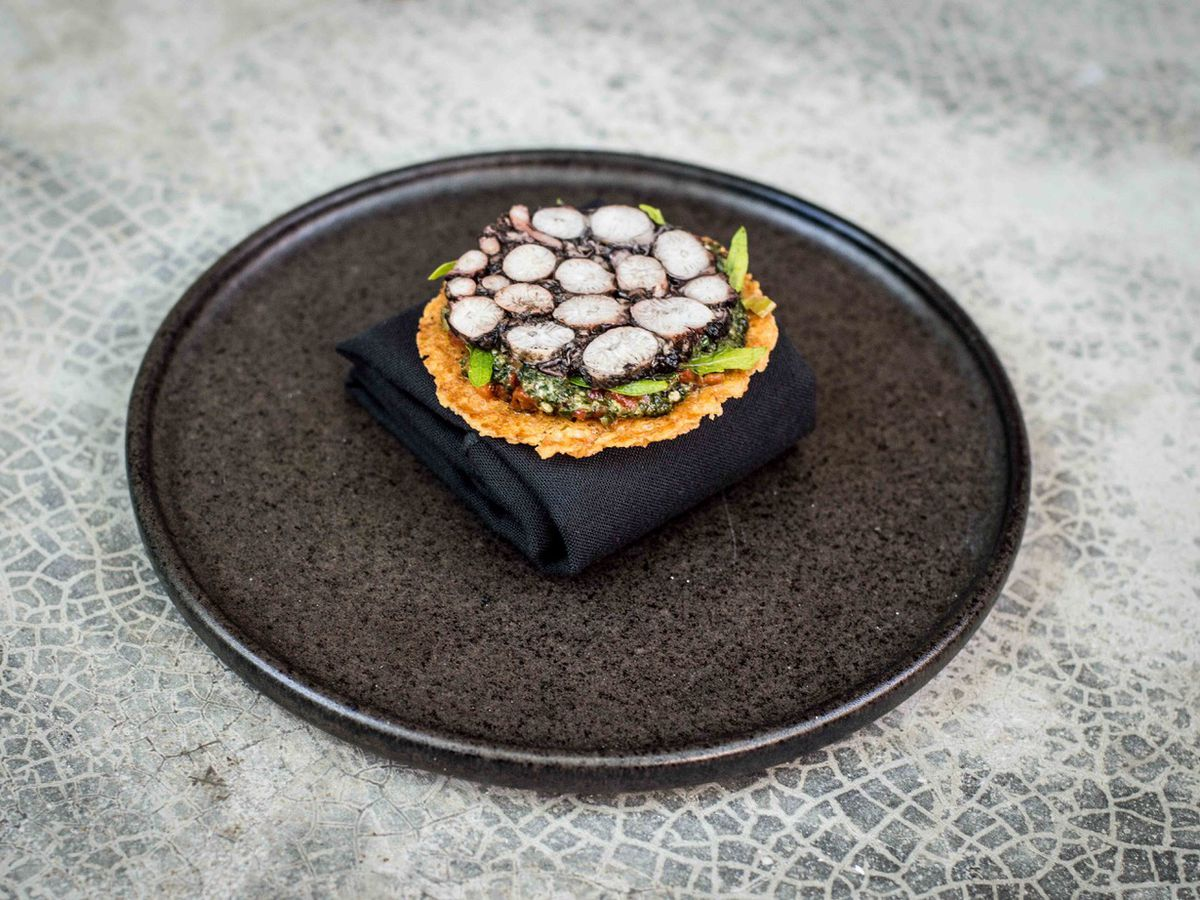 A layer of thin octopus terrine sits on top of various mashed vegetables on top of a charred tostada, all sitting on a black plate on a cement gray background.