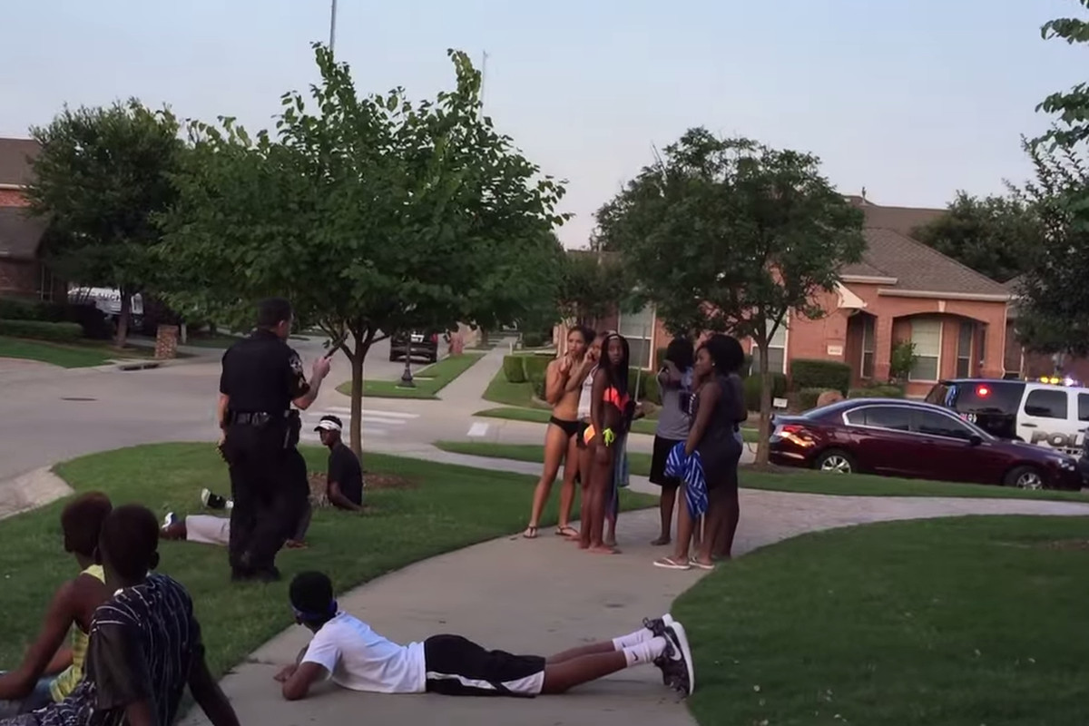 A police officer detains black teens at a McKinney, Texas, pool party.
