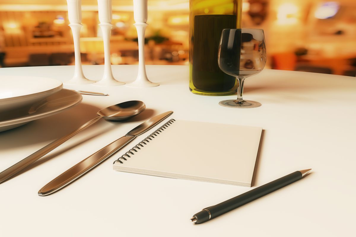 View of a table at a restaurant, with a blank notepad and a glass of wine.