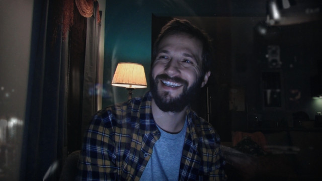 A man with a beard in a bedroom looks off-camera and laughs