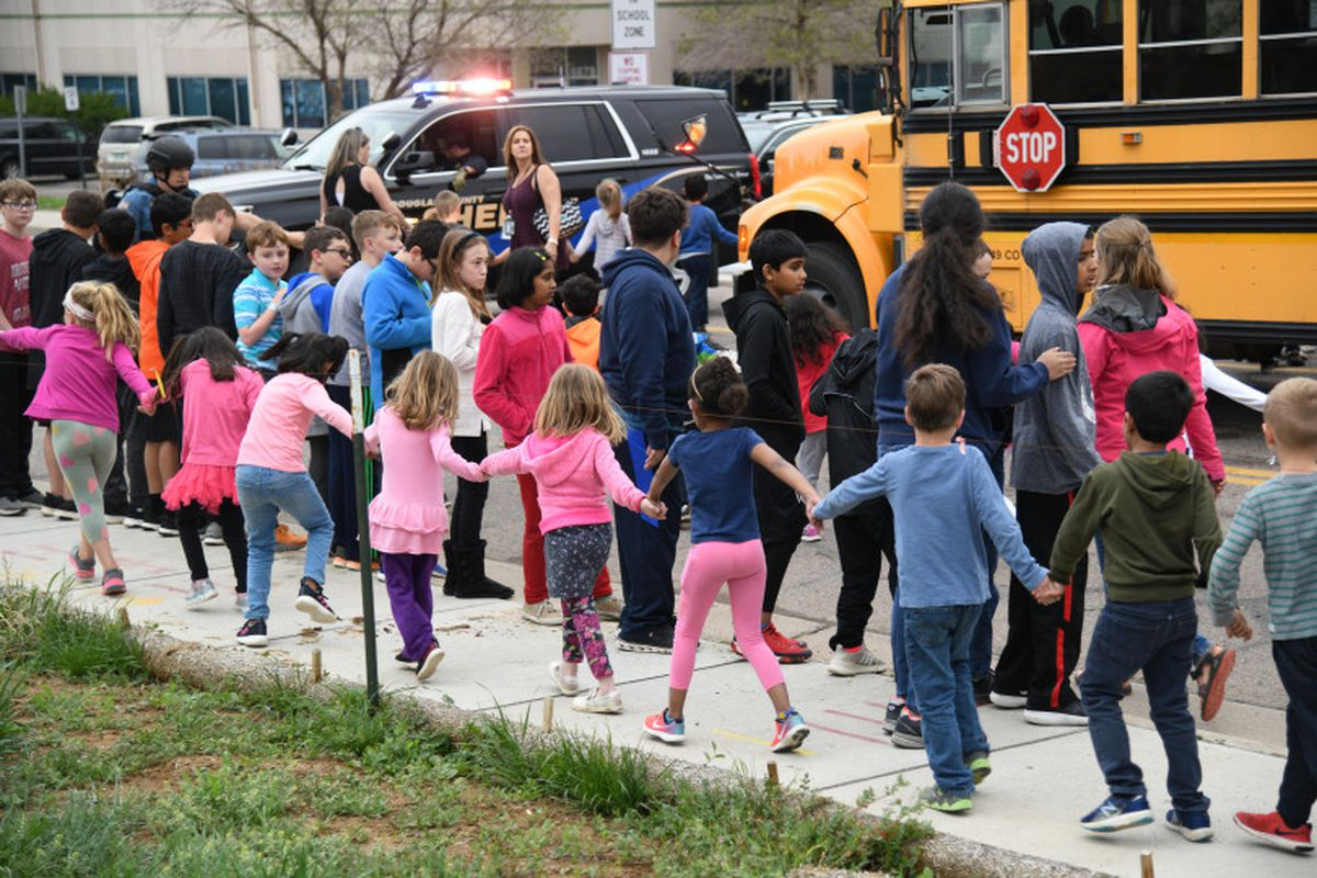 Students are escorted to a school bus in front of STEM School Highlands Ranch after a shooting.