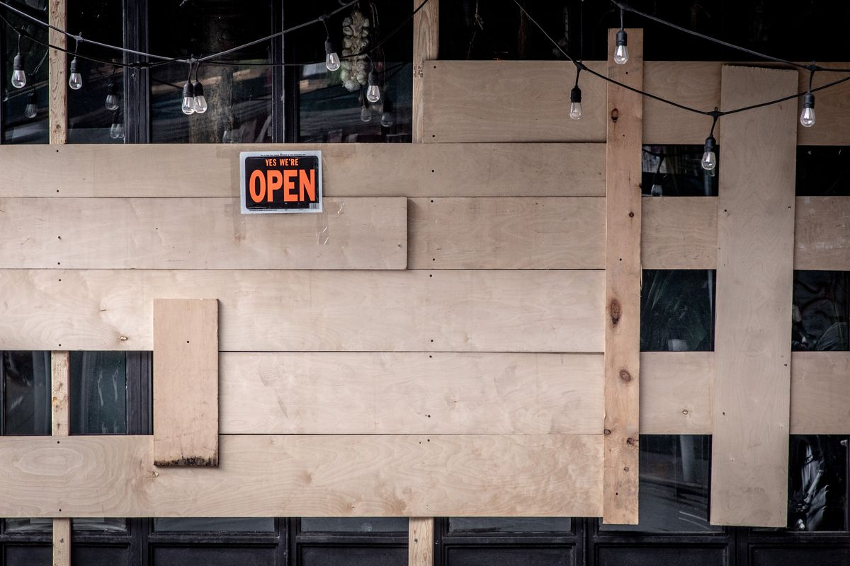 """A string of market lights hangs against a restaurant with boarded-up windows. Posted to it, there is a sign that reads, """"Yes we're open."""""""