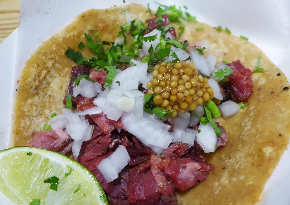A flat tortilla with chunks of red meat and a salsa that looks like fish eggs.