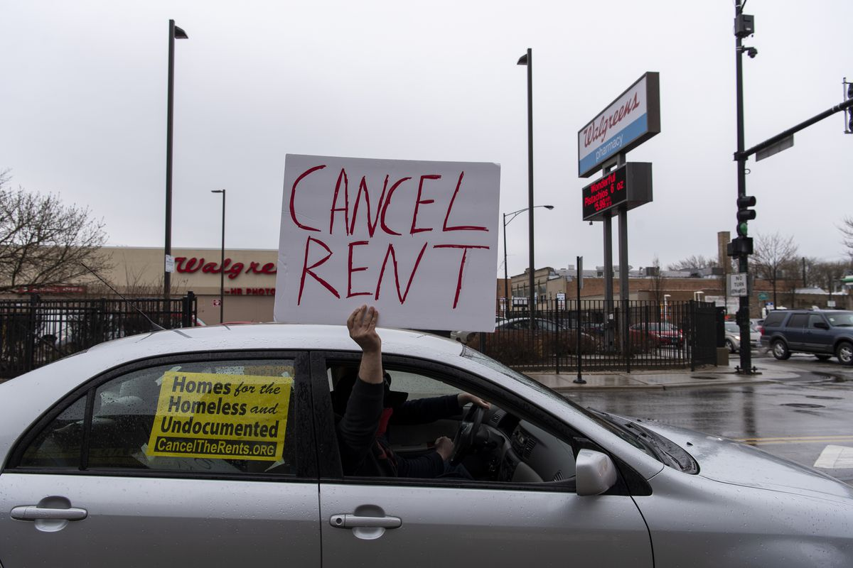 A man holds up a sign demanding that rent be canceled during a vehicle protest Saturday in the Albany Park neighborhood.
