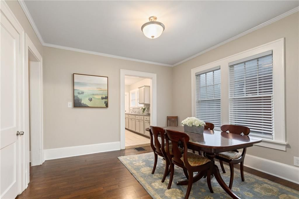 A dining room with off-white walls and a dining room table.