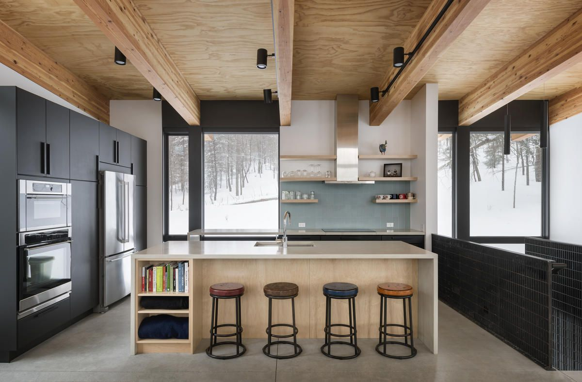 Kitchen with breakfast counter, timber ceiling, and black cabinetry.