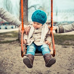 Sad child on a swing, inbetween her  divorced parents holding her separatedly .