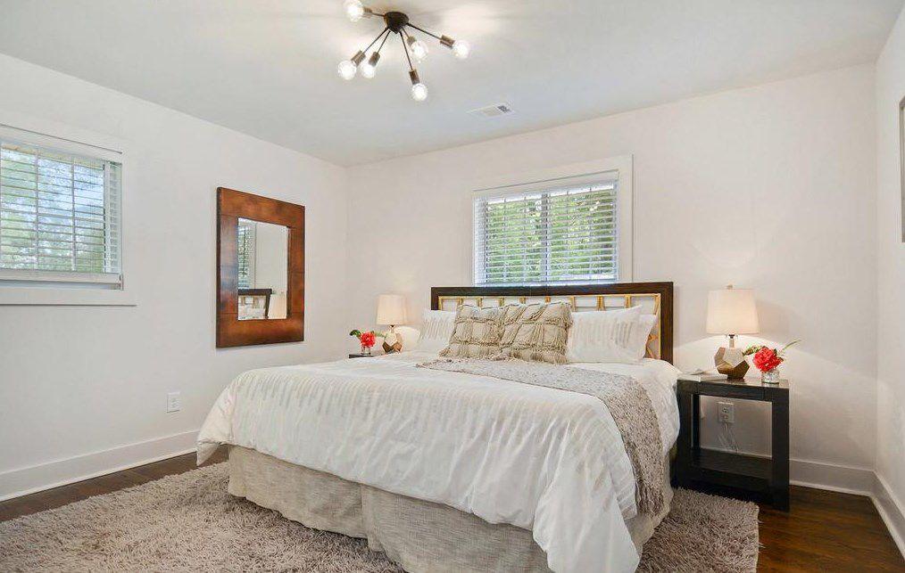 A white master bedroom with a sputnik light fixture.