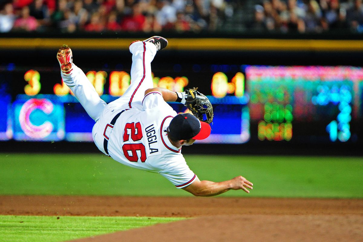 ATLANTA, GA - JULY 5: Dan Uggla #26 of the Atlanta Braves attempts to throw out a runner against the Chicago Cubs at Turner Field on July 5, 2012 in Atlanta, Georgia. (Photo by Scott Cunningham/Getty Images)