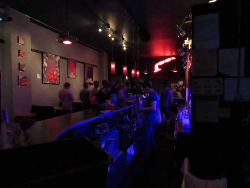 The interior of a bar. A bar counter bisects the photo with people working behind it on the right and customers on the left. The left wall is gray with art mounted on it.
