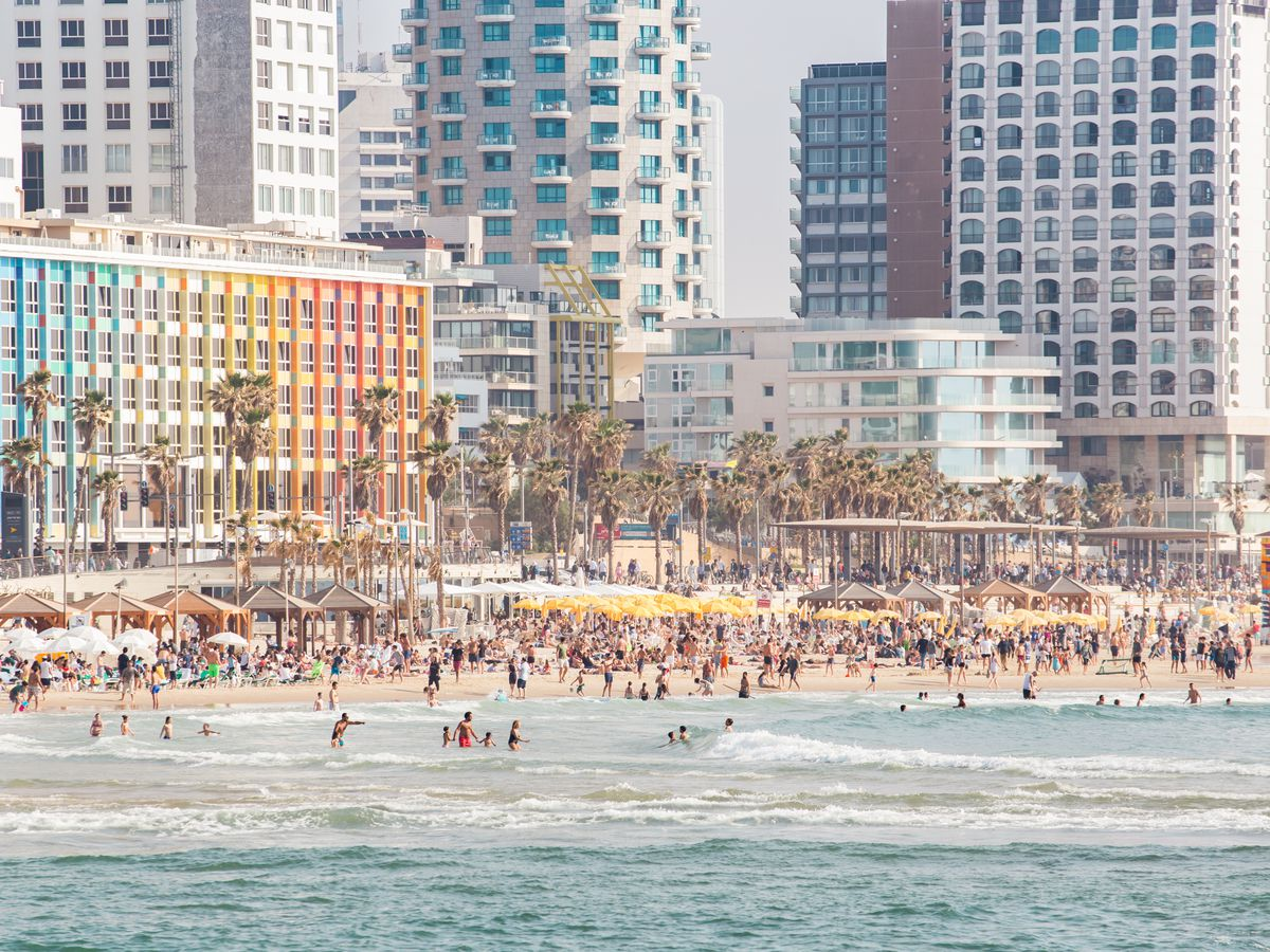 A beach area in Tel Aviv which is adjacent to many tall city buildings.