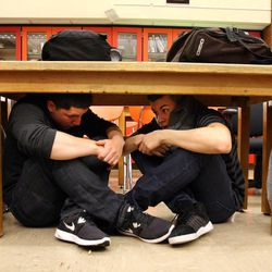 Javier Chavez, right, and Francisco Rubio, Taylorsville High School students in Steve Woolley's physics class, sit under their desks during an earthquake drill as part of The Great Utah ShakeOut, Tuesday, April 17, 2012.