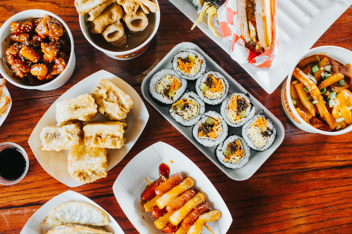 A spread of Korean dishes, including gimbap, rice cake skewers, and dumplings on a wood table.