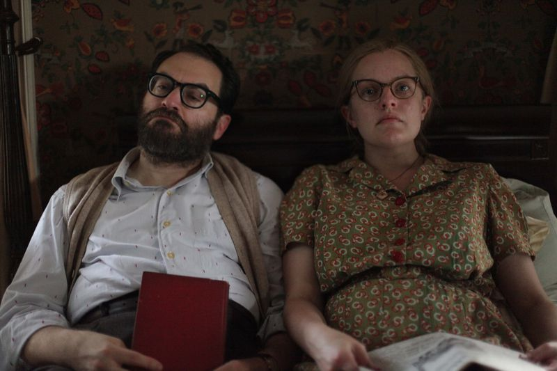 A middle-aged couple sits in bed.