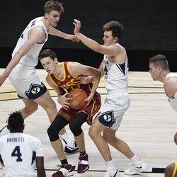 Southern California's Drew Peterson, looks to pass as he cuts between the defense of BYU's Matt Haarms, left, and Brandon Averette, second from right, during game, Tuesday, Dec. 1, 2020, in Uncasville, Conn.