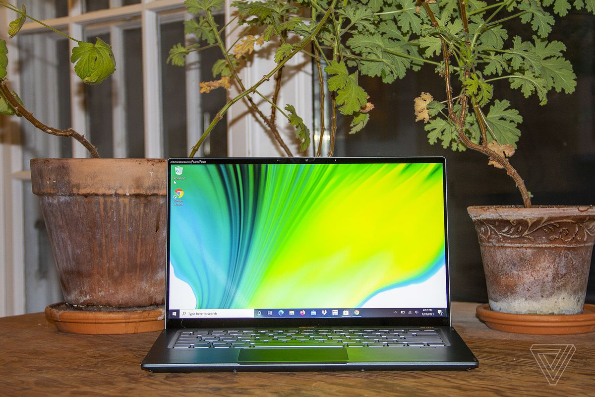 The Acer Swift 5 open, seen from the front. The screen depicts a green, blue, and white background.