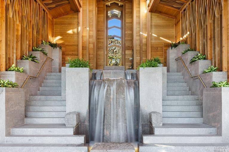 indoor waterfall flanked by staircase.