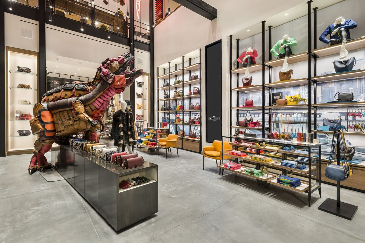 Colorful bags sitting on shelves next to a huge T-Rex constructed out of Coach handbags.