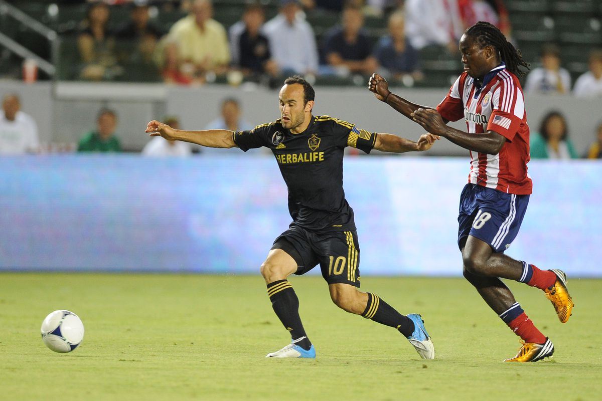 Aug 12, 2012; Carson, CA, USA; Los Angeles Galaxy midfielder Landon Donovan (10) moves the ball defended by Chivas USA midfielder Shalrie Joseph (18) during the first half at the Home Depot Center.  Mandatory Credit: Kelvin Kuo-US PRESSWIRE