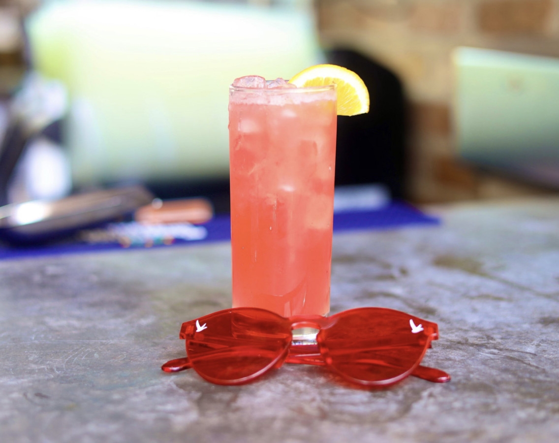 A pink cocktail with a lemon slice behind bright red sunglasses