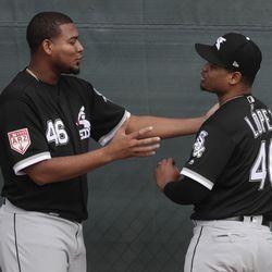 Chicago White Sox's Ivan Nova talks to Reynaldo Lopez during a spring training baseball workout Saturday, Feb. 16, 2019, in Glendale, Ariz.   Morry Gash/Associated Press