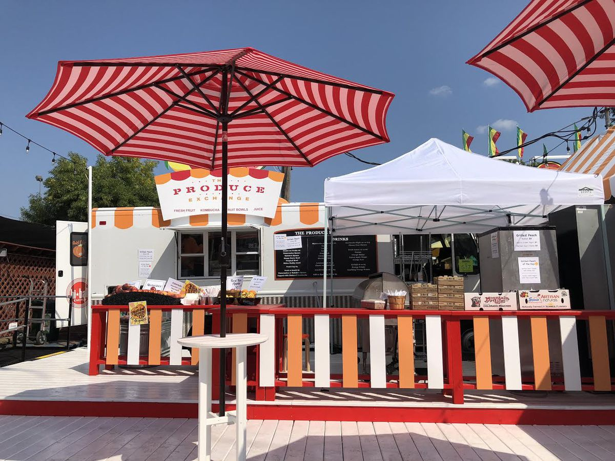A bright white stand with orange, white, and red picket fence surrounding it. A deck area is flanked by giant umbrellas