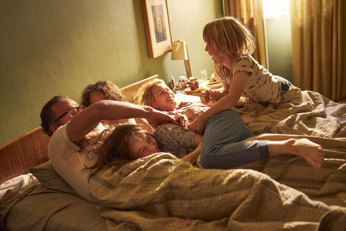 a family playing in bed