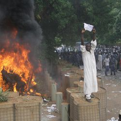 A Sudanese protester stands on a barricade during a demonstration in Khartoum, Sudan, Friday, Sept. 14, 2012, as part of widespread anger across the Muslim world about a film ridiculing Islam's Prophet Muhammad. Germany's Foreign Minister says the country's embassy in the Sudanese capital of Khartoum has been stormed by protesters and set partially on fire. Minister Guido Westerwelle told reporters that the demonstrators are apparently protesting against an anti-Islam film produced in the United States that denigrates the Prophet Muhammad.