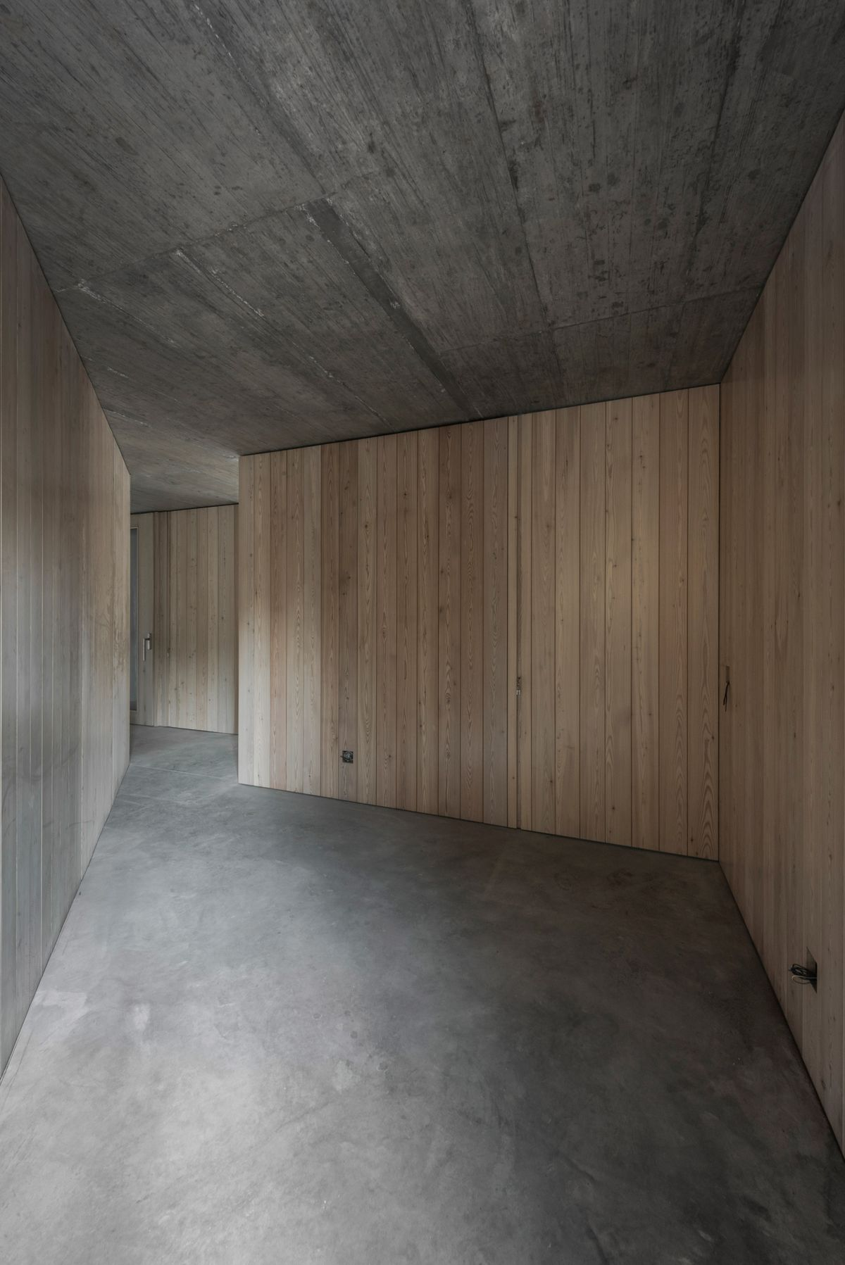 Corridor with raw timber walls and concrete floor and ceiling.