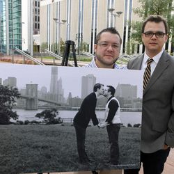 Tom Privitere, left, and his partner Brian Edwards pose at the federal courthouse in Denver on Wednesday, Sept. 26, 2012, with the engagement photo that was altered and used in a political campaign. The New York skyline was replaced with a winter scene. They and the photographer who took the photo have filed a lawsuit over the misuse of the photograph.