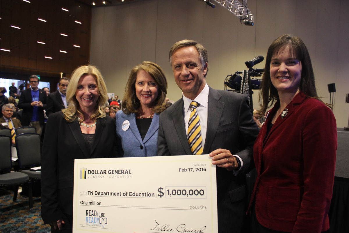 Dollar General's Denine Torr (left) presents a gift for the state's literacy work to first lady Chrissy Haslam, Gov. Bill Haslam and Education Commissioner Candice McQueen.