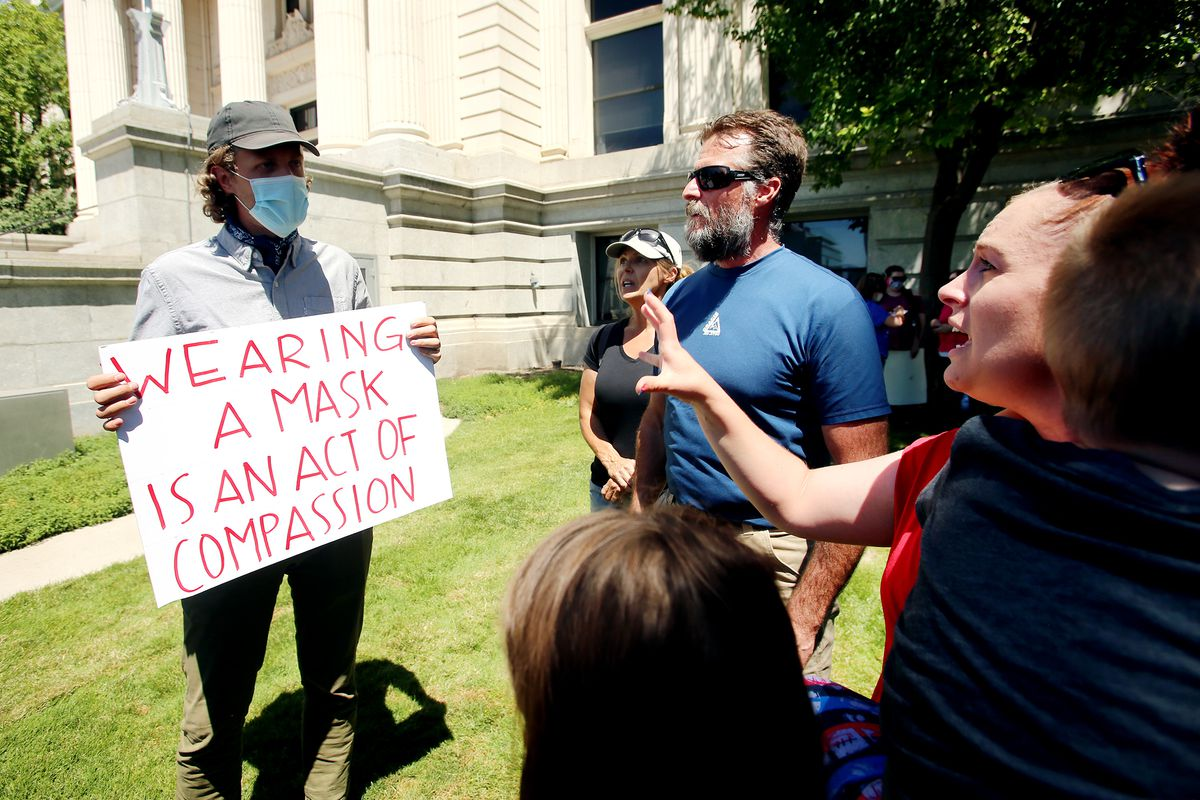 """Clark Goldsberry, a high school teacher at American Fork High School listens as Nicole Holley and others question him on why he wears a mask outside of the Utah County Administration Building inProvo on Wednesday, July 15, 2020. The Utah County Commission was scheduled to vote on a letter asking Ralph Clegg, executive director of the Utah County Health Department, to give Utah County """"compassionate exemptions"""" to Gov. Gary Herbert's mask mandate for K-12 schools. However, the meeting was cut short after Tanner Ainge, the commission's chairman, made a motion to continue the meeting at a later date, saying it violated several public health directives issued by the state and county. The motion to reschedule passed 2-1, bringing boos from protesters."""