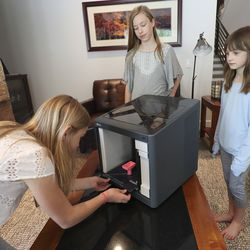 Sofia, left, Ella and Anna Gelston, daughters of L3Harris division president Dan Gelston, demonstrate how they used a 3D printer to make a part for positive air pressure respirators at their home in Park City on Friday, April 24, 2020. Over 100 L3Harris engineers and employees assembled 1,200 positive air pressure respirators to donate to the University of Utah Health to protect medical first responders during the coronavirus pandemic.