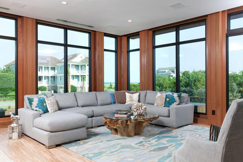 A different view of the living room shows a large gray sectional couch in front of tall windows.