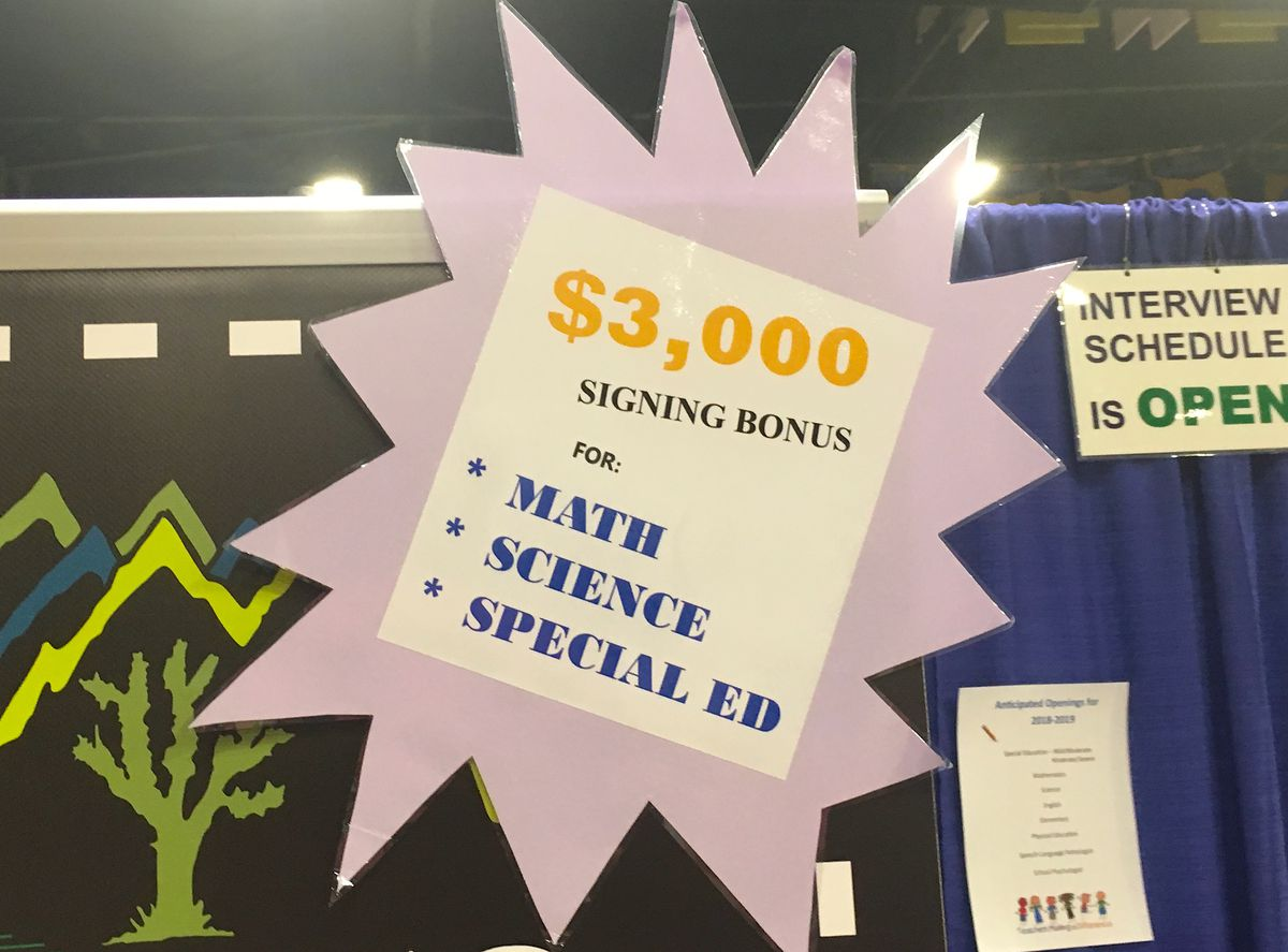 A sign at a job fair booth advertising signing bonuses for certain positions