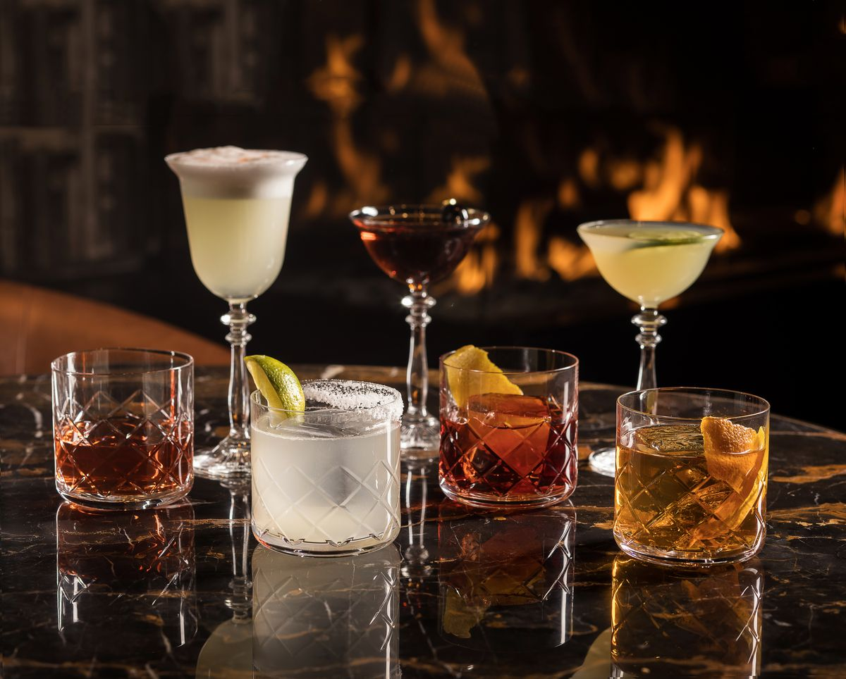Seven cocktails in front of a fireplace