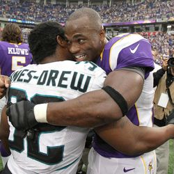 Minnesota Vikings running back Adrian Peterson, right, hugs Jacksonville Jaguars running back Maurice Jones-Drew after his team's 26-23 overtime victory in an NFL football game on Sunday, Sept. 9, 2012, in Minneapolis.