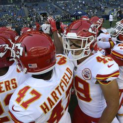 Kansas City Chiefs players, including Marcus Peters (22), Trevon Hartfield (47), and Daniel Sorensen (49), huddle on the field during warmups before an NFL football preseason game against the Seattle Seahawks, Friday, Aug. 25, 2017, in Seattle. (AP Photo/Elaine Thompson)