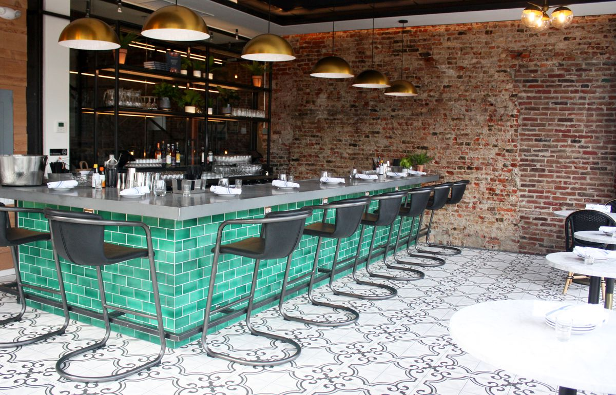 bar with green tile and exposed brick wall