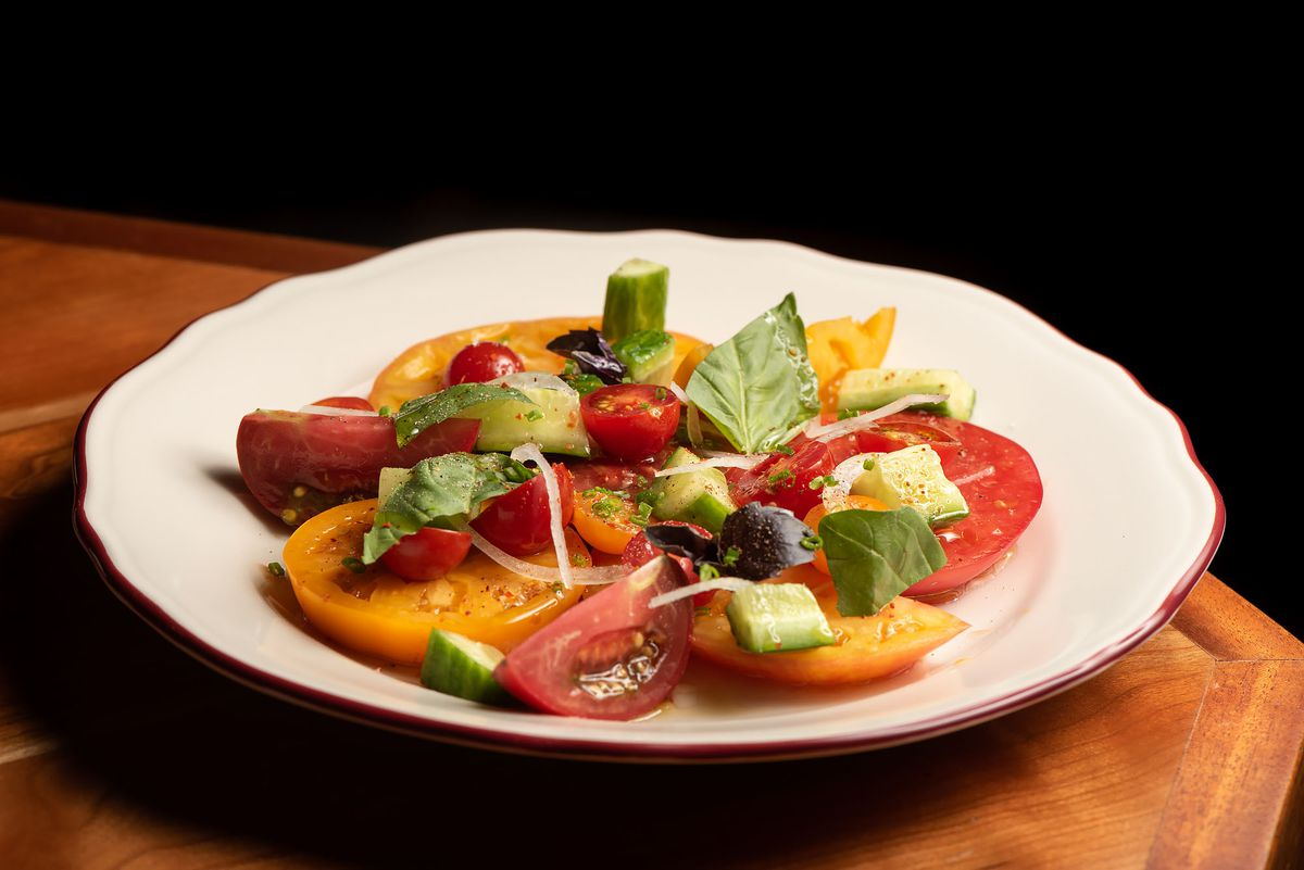 A bright tomato and onion salad on a table.