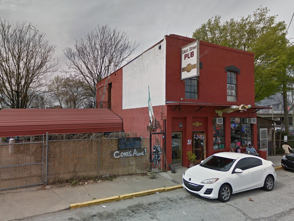 The exterior of a pub. The facade is painted red. There is a white sign in front of the pub that reads: pub.